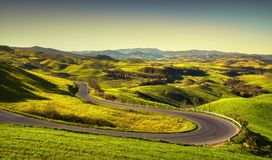 Tuscany landscape, road and green field. Volterra Italy. Tuscany landscape, hairpin bend road and green field at sunrise. Volterra Italy Europe Stock Image