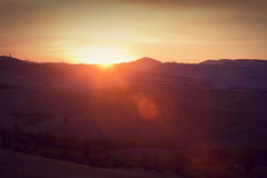 Tuscany landscape at sunrise, Italy. Tuscan hills, sun flare Royalty Free Stock Photo
