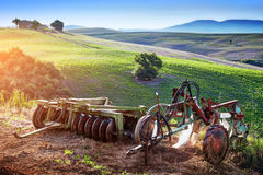 Tuscany landscape at sunrise. Retro agriculture machines. Italy Stock Photo