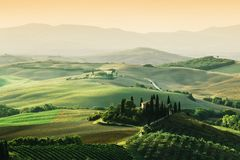 Tuscany landscape at sunrise. Tuscan farm house, vineyard, hills. Stock Photos
