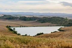 Tuscany landskap av en sjö och mjuka kullar Arkivbilder