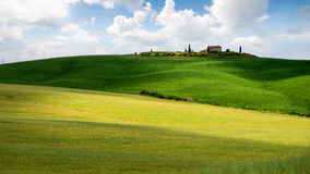 Tuscany landskap, litet hus överst av en kulle mot blå himmel arkivbilder