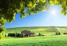 Tuscany landskap med lantgårdhuset Arkivbilder