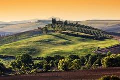 Tuscany liggande på soluppgången Tuscan lantgårdhus, gröna kullar arkivbilder