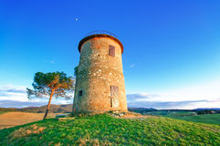 Tuscany, Maremma sunset landscape. Rural tower and tree on hill. Royalty Free Stock Images