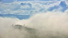 Tuscany misty morning in spring time with farmer home. Tuscany misty morning in spring time with farmer house in the clouds stock photos