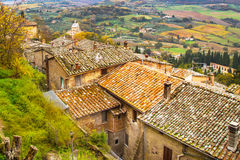 Tuscany panoramic landscape with old traditional houses roofs, cypress, vineyards,  Italy Stock Photos