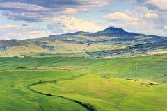 Tuscany, Radicofani wioska, ziemia uprawna i zieleni pola, Val d Lub Zdjęcia Stock
