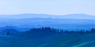 Siena, rolling hills on blue sunset. Rural landscape with cypress trees. Tuscany, Italy Royalty Free Stock Image