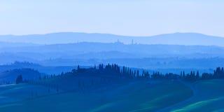 Siena Rolling Hills på blåttsolnedgång. Lantligt landskap med cypresstrees. Tuscany Italien Royaltyfri Bild