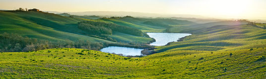 Tuscany, rural landscape on sunset, Italy. Lake and green fields Royalty Free Stock Photo