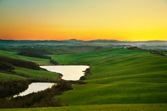 Tuscany, rural landscape on sunset, Italy. Lake and green fields. Tuscany, Crete Senesi landscape near Siena, Italy, europe. Small lake, green and yellow fields Stock Photo
