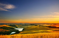 Tuscany, rural landscape on sunset, Italy. Lake and green fields Royalty Free Stock Photos