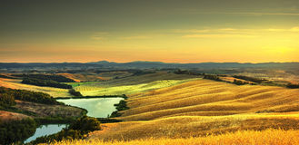 Tuscany, rural landscape on sunset, Italy. Lake and green fields Stock Images