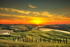 Tuscany, rural sunset landscape. Countryside farm, white road an Stock Photos