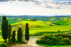 Tuscany, rural sunset landscape. Countryside farm, white road an Royalty Free Stock Photo