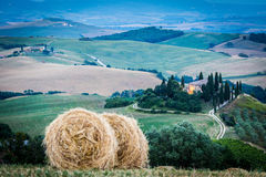 Tuscany after sunset, Italy. Tuscany, Italy. Magic night view of the country with farmhouse and bale of hay, green hills Royalty Free Stock Photo