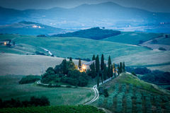 Tuscany after sunset, Italy. Tuscany, Italy. Magic night view of the country with farmhouse and bale of hay, green hills Stock Images