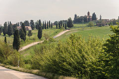 Tuscany Valley with Single Lane Road. A wide angle view of a green valley in Tuscany with a single lane road in between Royalty Free Stock Image
