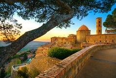 Tuscany, Volterra stadhorisont, kyrka och träd på solnedgång ital arkivfoto