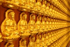 Tusen av den små guld- Buddha statyn Arkivbild