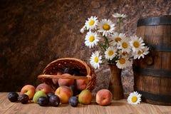 Tusenskönan blommar i en vas med nya frukter i en vickerkorg Arkivbilder