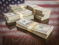 Tusentals dollar med reflexion av amerikanska flaggan på tabellen Arkivfoton