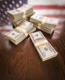 Tusentals dollar med reflexion av amerikanska flaggan på tabellen Arkivfoto