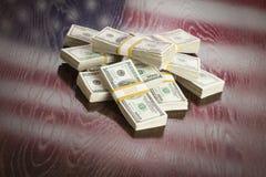 Tusentals dollar med reflexion av amerikanska flaggan på tabellen Fotografering för Bildbyråer