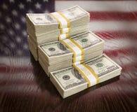 Tusentals dollar med reflexion av amerikanska flaggan på tabellen Royaltyfri Bild