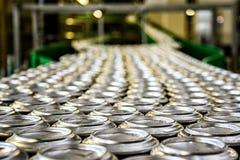Tusentals dryckaluminiumburkar på transportör fodrar på fabriken Arkivbilder