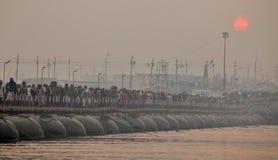 Tusentals hinduiska fantaster som korsar pontonbroarna över Gangeset River på den Maha Kumbh Mela festivalen arkivbild