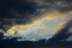 Tussen de donkere wolken backlit door de zonsondergang is er het hoogtepunt Stock Foto's