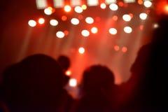 Tussen mensen voor een stadium met onscherpe stadiumverlichting bokeh Royalty-vrije Stock Foto