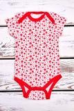 Tuta bianca e rossa della neonata Immagini Stock