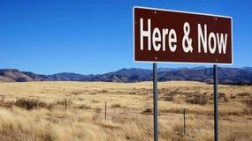 Tutaj i Teraz brown drogowy znak zdjęcie stock