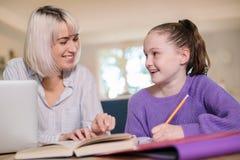 Tuteur à la maison féminin Helping Young Girl avec des études image libre de droits