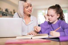 Tuteur à la maison féminin Helping Young Girl luttant avec des études images stock