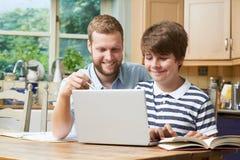 Tuteur à la maison masculin Helping Teenage Boy avec des études photographie stock