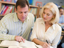 Free Tutor Assisting Mature Student In Library Royalty Free Stock Photo - 5947585