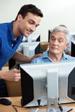 Tutor Assisting Senior Man In Using Computer At Classroom Royalty Free Stock Photography