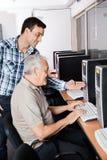 Tutor Assisting Senior Man In Using Computer. Male tutor assisting senior men in using computer at classroom Royalty Free Stock Photo