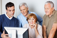 Tutor Assisting Senior People In Using Computer At Class Stock Photo