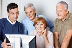 Tutor Assisting Senior People In Using Computer At Class. Male tutor assisting senior people in using computer at class Stock Photo