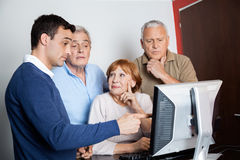 Tutor Assisting Senior People In Using Computer At Classroom Stock Images