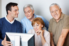 Tutor Assisting Senior Students In Using Computer At Class Royalty Free Stock Photo