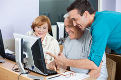 Tutor Assisting Senior Students In Using Computer At Class Stock Photography