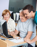 Tutor Assisting Senior Students In Using Computer At Classroom Stock Photography