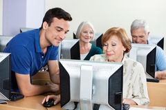 Tutor Assisting Senior Woman During Computer Class. Male tutor assisting senior women with classmates in background during computer class Stock Images