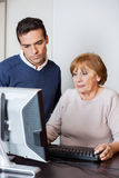 Tutor Assisting Student Using Computer In Lab stock image